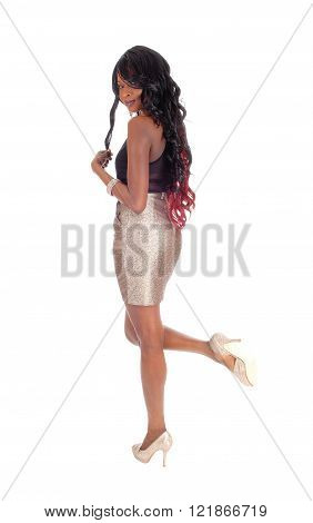 A beautiful African American woman is a gold color skirt and black blouse with long black hair standing in profile isolated for white background.