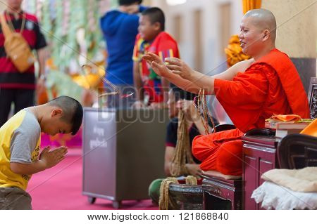 SANGKHLABURI, THAILAND, JANUARY 24, 2016 :  A skilled Buddhist monk is blessing a man  by throwing a rosary necklace around his neck in the Wat Wang Wiwekaram temple, Sanghklaburi, Thailand