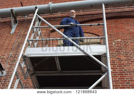 A painter and decorator working from a scaffold tower