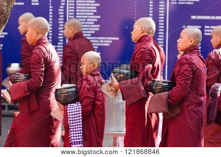 AMARAPURA, MYANMAR, JANUARY 20, 2015 : Young monks are queuing holding their bowls to collect the unique daily meal at noon in the Mahagandayon monastery near Mandalay, Myanmar (Burma).