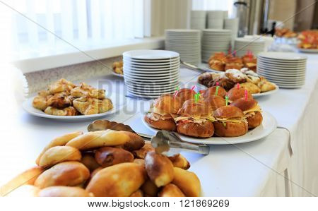 Catering banquet table with baked food snacks sandwiches cakes and plates self serve open buffet dinner selective focus horizontal view