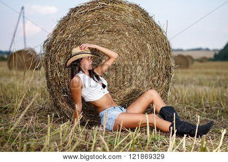 Woman in cowboy hat sitting near a straw bale