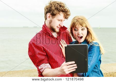 Suprised couple with tablet at seaside. Vacations, fun and technology concept.