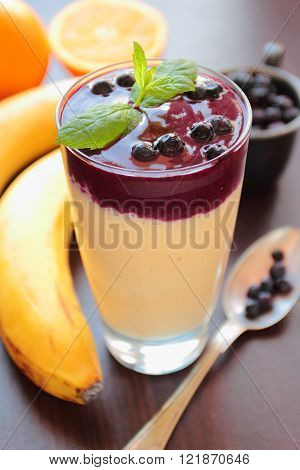 Two-color smoothie with banana orange and blueberries fruits in a glass