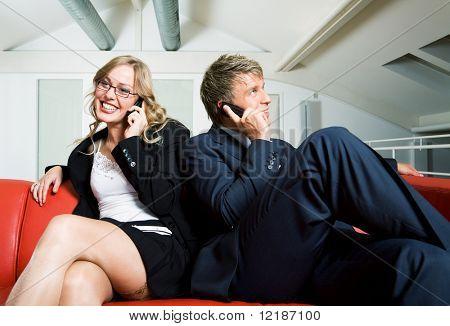 Una pareja, ambos sonriendo y hablando con sus teléfonos móviles