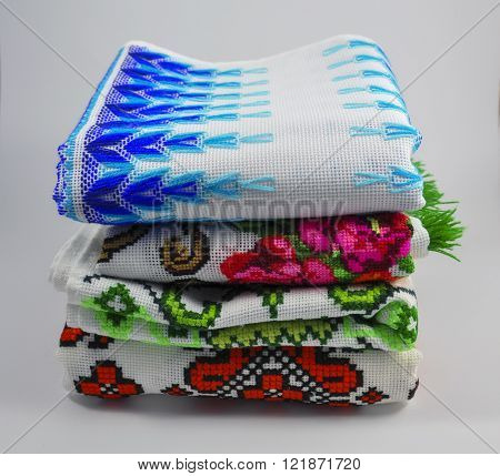 pile of embroidered towels on a white background