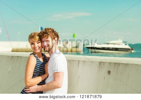 Travel tourism and people concept. Young tourist couple on vacation standing in front of boats sea water