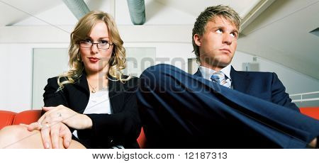Business couple on a sofa rather bored