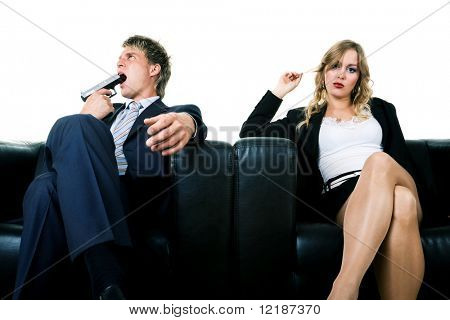 A couple on a sofa. He threatens to kill himself, she ignores him. A metaphor for divorce, lovesickness, or such things