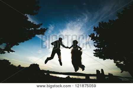 groom and bride jumping against the beautiful sky, silhouettes