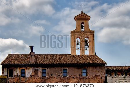 The basilica of Santi Cosma e Damiano is a church in the Roman Forumparts of which incorporate original Roman buildings. Tower of belfry and cloudy sky.
