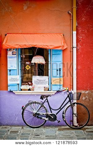 BURANO, VENICE, ITALY - MARCH 10: Lonely bicycle in the colorful street of island Burano, Venice