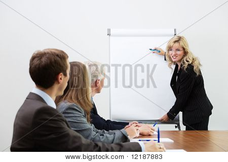 Businessteam listening to a coach giving a presentation on a flip chart (focus on coach)