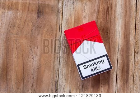 PHARE THAILAND - MARCH 9 2016. Pack of Marlboro Cigarettes on Wooden Table made by Philip Morris. Marlboro is the largest selling brand of cigarettes in the world.