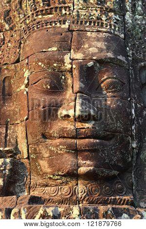 Giant stone face at Bayon Temple at sunset, Angkor Wat, Cambodia
