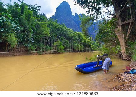 KHAO SOK, THAILAND - NOV 13, 2012: Unidentified man at the canoe trip on Khao Sok National Park. The park is the largest area of virgin forest in southern Thailand, older than the Amazon rain forest.