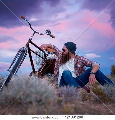 bearded wonderer sitting on suitcase beside bike in desert with dark sky