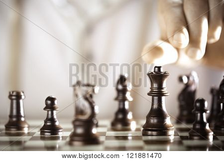 Board game chess player hand about to play excellence concept.
