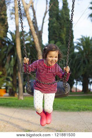 Happy three year old girl having fun on a swing