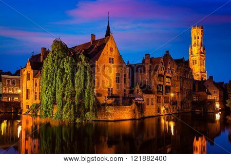 Famous view of Bruges - Rozenhoedkaai with Belfry and old houses along canal with tree in the night. Brugge, Belgium