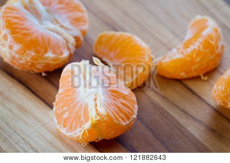 close up of a small orange or tangerine on a wooden cutting board