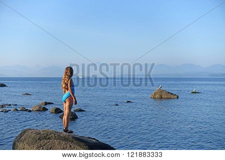 Girl looking at sail boat on Quadra Island,BC,Canada.