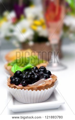 Small cakes with currant on white long plate.