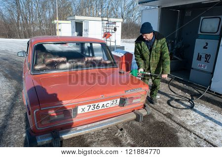 Krasnodar Russia - January 21 2015: Middle-aged man in camouflage clothing runs the old car on a rural gas station gasoline AI-92 in the winter on a sunny day.