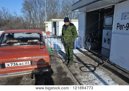 Krasnodar, Russia - January 21, 2015: Middle-aged man in camouflage clothing runs the old car on a rural gas station gasoline AI-92 in the winter on a sunny day.