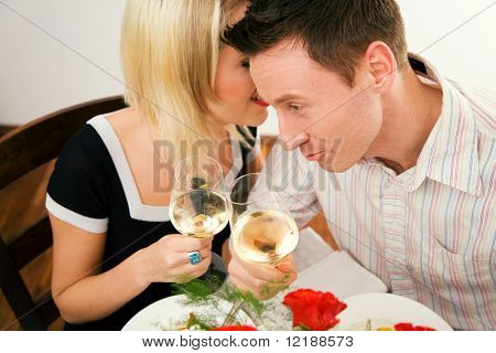 Young couple romantic dinner: both holding white whine glasses, she is whispering something; focus on his face