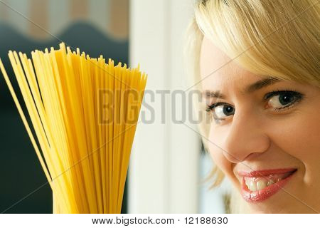 A woman with uncooked spaghetti (going to prepare them presumably)