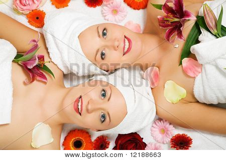 Two girls relaxing in a wellness set-up seen from above, horizontally  aligned, with lots of flowers, open eyes, smiling