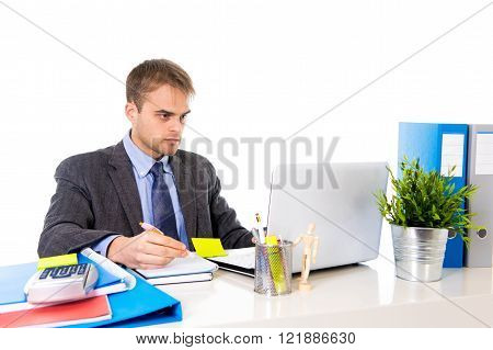 young attractive businessman working busy with laptop computer writing on pad with pen at office desk in business project success concept isolated on white background