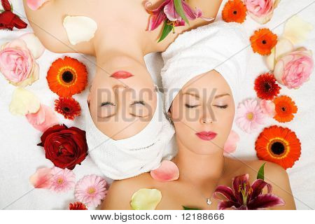 Two girls relaxing in a wellness set-up seen from above, vertically aligned, with lots of flowers, closed eyes