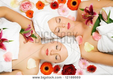 Two girls relaxing in a wellness set-up seen from above, horizontally  aligned, with lots of flowers, closed eyes