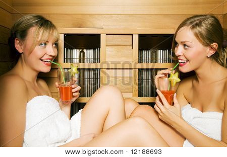 Dos amigos (mujer) disfrutando vitaminadas en un sauna