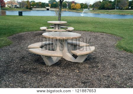 Small picnic tables are available next to a small suburban lake