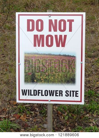 LEESBURG, FLORIDA - February 22: on February 22, 2016, a sign stating Do Not Mow Wildflower Site stands at Palatlakaha Environmental and Agricultural Reserve (PEAR) Park in Leesburg, Florida.