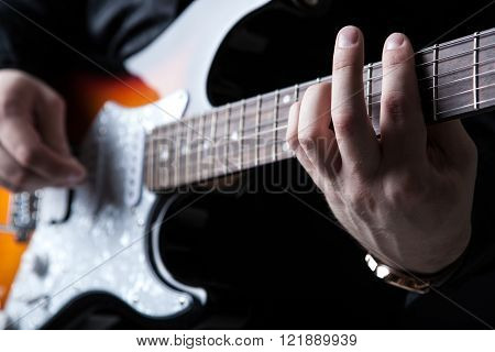 guitarist playing guitar on a black background ** Note: Shallow depth of field
