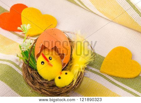 Easter decoration: hen with chicken in the nest and three felt hearts on cotton napkin. Main colors: yellow white green orange.