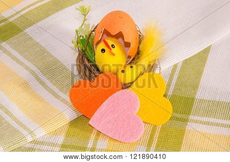 Easter decoration: hen with chicken in the nest and three colorful felt hearts on cotton napkin. Main colors: yellow, white, green, orange, pink.