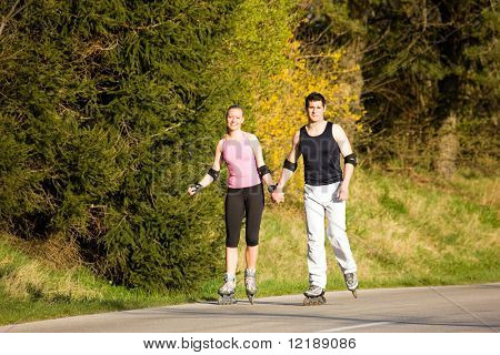 Beautiful young people rollerblading at a spring afternoon