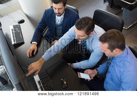 Business team analyzing data on computer.