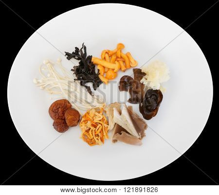 Asian mushrooms on plate, isolated over black with clipping path