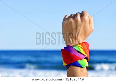 closeup of a young caucasian man with his fist raised to the sky and a kerchief patterned as the rainbow flag tied in it, with the ocean in the background
