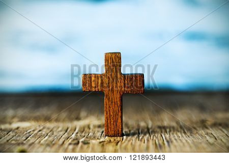 closeup of a small wooden cross on a rustic wooden surface