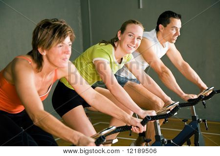Three People Cycling In A Gym Or Fitness Club, Dressed In Colorful Clothes; Focus On Girl In The Middle