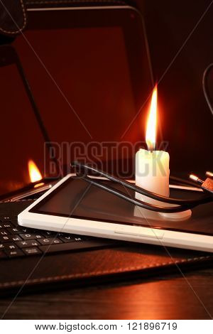 Blackout concept. Lighting candle on laptop and tablet