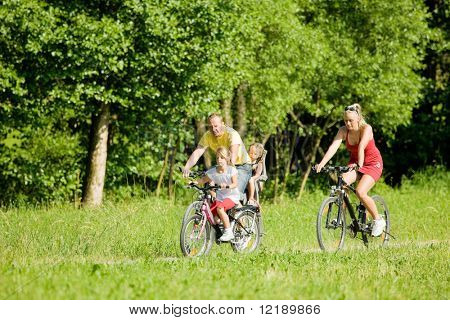 Family with two kids riding their bicycles on a summer day