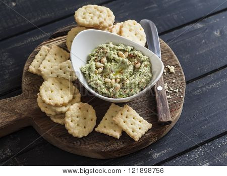Healthy vegetarian broccoli and pine nuts hummus and homemade cheese biscuits on a wooden rustic board. Delicious snack or appetizer with wine